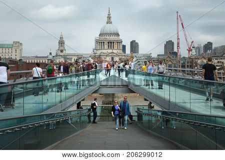 LONDON, UK - MAY 29 , 2017:  Tourists walking across the Millenium bridge to St. Paul Cathedral by a cloudy day in London