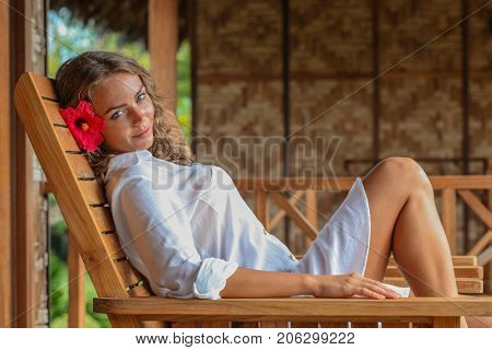 Young woman relaxing on tropical resort sitting on chaise lounge