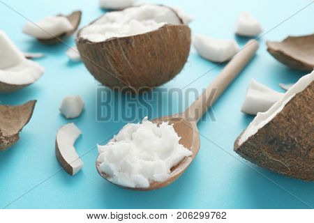Composition with fresh coconut oil in spoon on color background