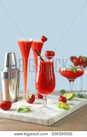 Glasses of delicious strawberry daiquiri on table