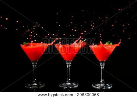Glasses of delicious strawberry daiquiri with splash on black background