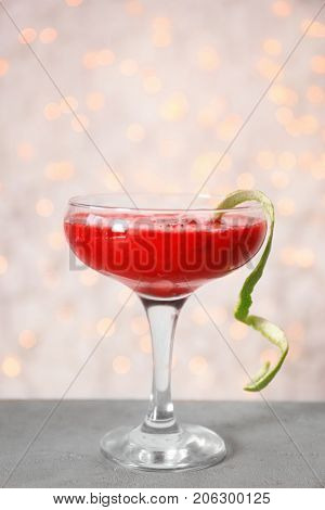 Glass of delicious strawberry daiquiri on table against defocused lights