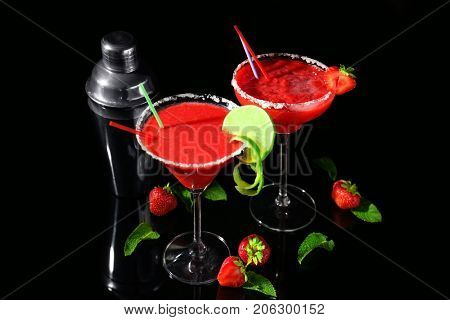 Glasses of delicious strawberry daiquiri on black background