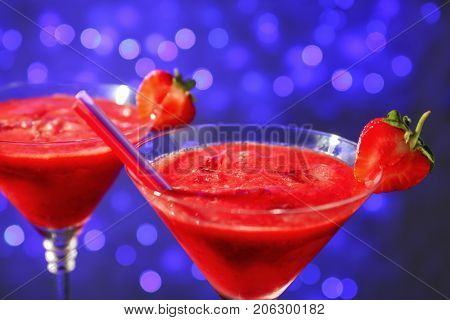 Glasses of delicious strawberry daiquiri against defocused lights
