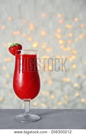 Glass of delicious strawberry daiquiri on table against blurred lights