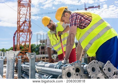 Two efficient blue-collar employees preparing supplies before building a metallic scaffolding while working together on the construction site