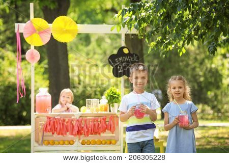 Adorable little children with jars of homemade lemonade in park