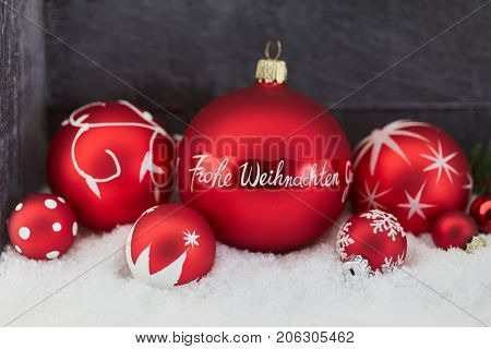 Frohe Weihnachten (Merry Christmas) as background decoration with red christmas balls