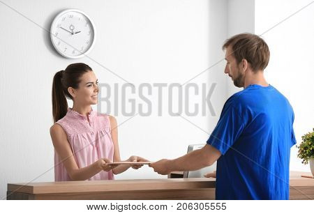 Young female receptionist meeting client in office