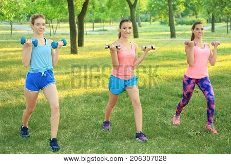 Young sporty women with dumb-bells doing exercise outdoors