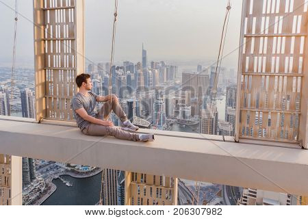 Roofer sits on concrete cross beam of Cayan Tower (Infinity Tower) in Dubai, UAE