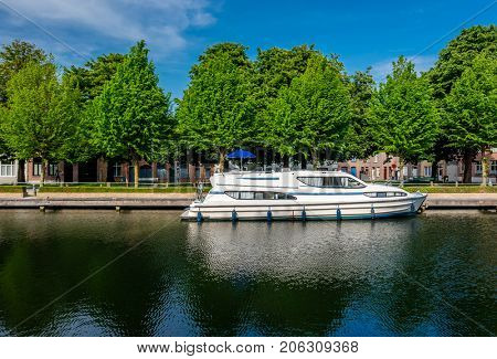 Bruges (Brugge) cityscape with water canal and motor boat, Flanders, Belgium