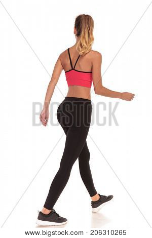 back view of a walking woman fitness instructor looking to side on white background