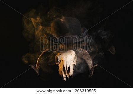 Ram skull with horns in a bowler hat, Halloween theme