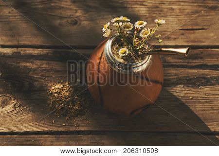 High angle view of  Argentinean yerba mate drink with chamomile flowers