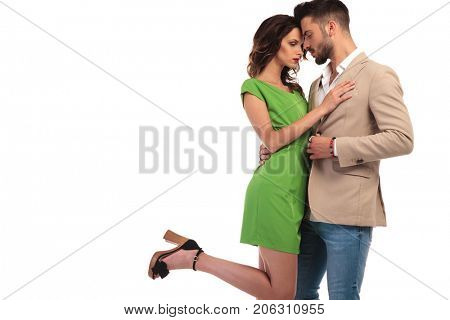 hot couple standing embraced and look at each other on white background, woman with one leg up in the air