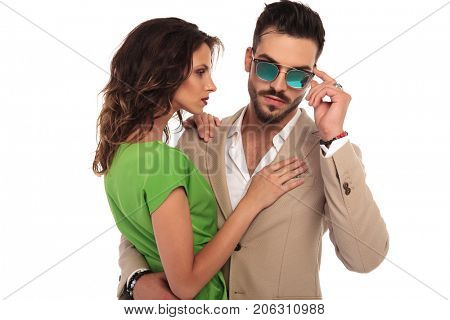 sexy man fixing sunglasses while embracing his woman; young elegant couple standing embraced on white background