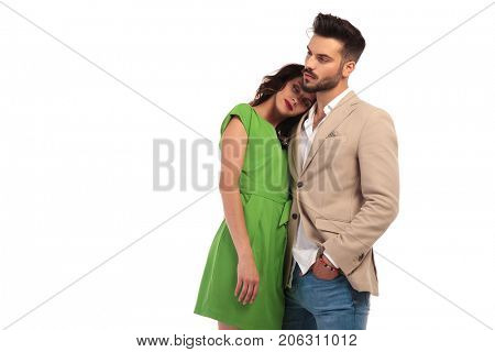woman in green dress leaning head on lover's shoulder on white background