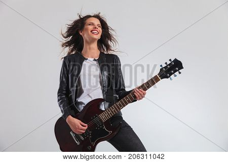 laughing woman guitarist enjoying herself while playing electric guitar on grey background
