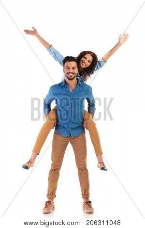 excited young casual couple standing on white background, man carrying woman while she is with hands in the air