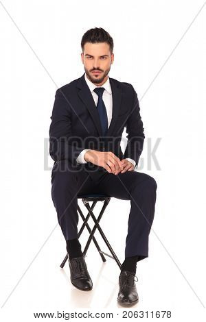 young un shaved business man is sitting on chair on white background
