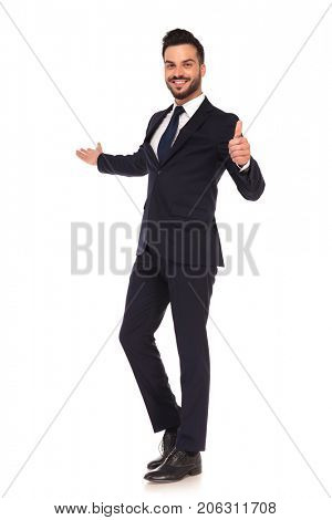 smiling confident young business man presenting and making the ok hand sign on white background