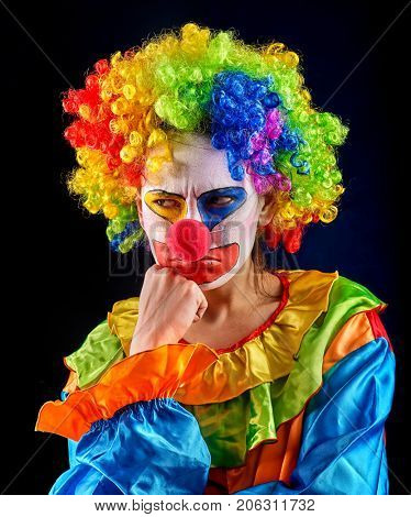 Evil clown on black background. Portrait of mad woman with angry look. Person is tired of working with children.