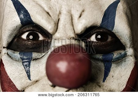 closeup of a scary evil clown with a disturbing look in his eyes