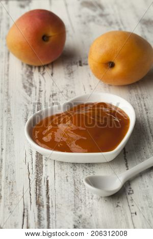 Bowl with homemade apricot jam and fresh fruit on the background