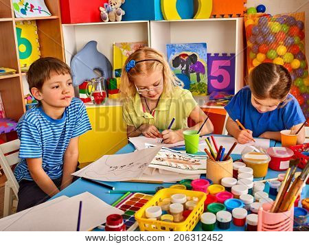 Small students painting in art school class. Child drawing by paints on table. Boy and girls in kindergarten. Preparing for a children's art exhibition.
