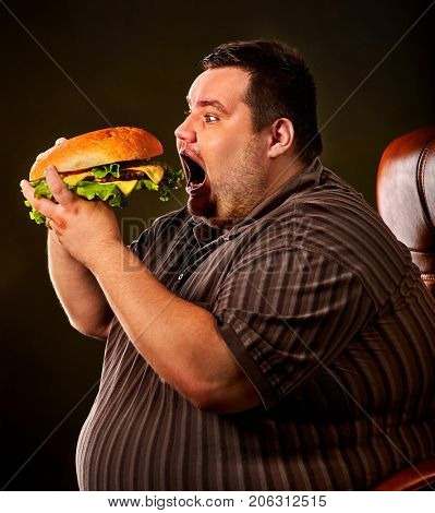 Diet failure of fat man eating fast food hamberger. Happy smile overweight person who spoiled healthy food by eating huge hamburger on fork. Hate to diets. Very fat man eating fast food.