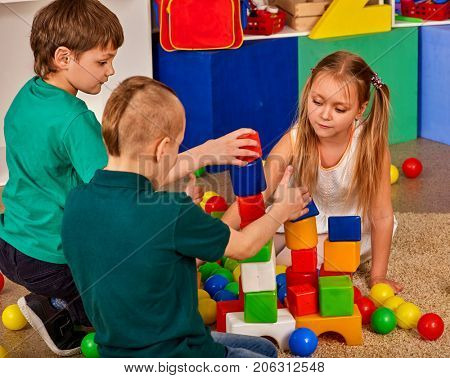 Children building blocks in kindergarten. Group kids playing toy on floor. Top view of interior preschool. Children develop their fingers in a game of cubes. Logical constructor.