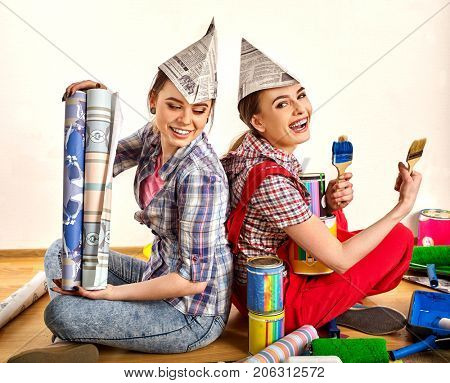 Repair home women holding painting tools roller for wallpaper and paint bank for wall. Happy girls wearing newspaper hat renovation apartment in room. Girlfriends started repairing house.
