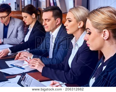 Business people office life of team people working with papers sitting table. Cabinets with folders background. Joyful business team in office discussing, sitting at table. They earn on Forex.
