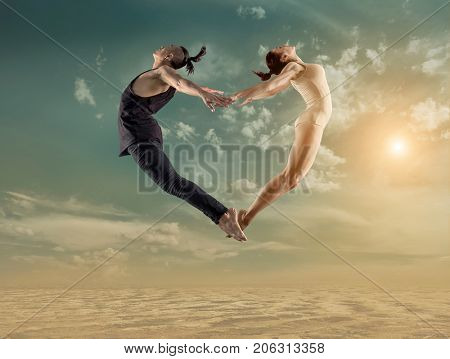 Two person, dancers, woman and man in dynamic jump action  heart figure under sunlight in sunny day under blue sky.