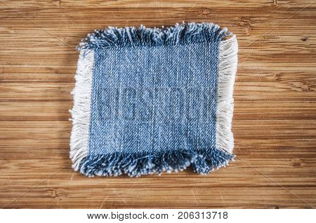 Destroyed torn denim blue jeans frayed flap patch fabric on wooden background