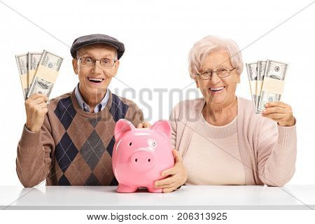 Happy seniors with money bundles and a piggybank seated at a table isolated on white background
