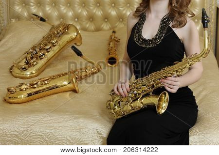 Woman in black dress sits with sax on bed with wind instruments, noface