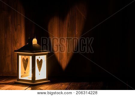 Lantern with heart shaped glass and burning candle inside on wooden background with copyspace for Valentines or Christmas