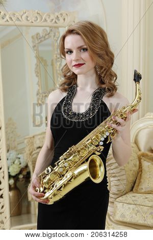 Pretty woman in black dress with sax poses in baroque studio with big mirror