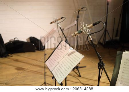 Professional microphones, notes in modern empty sound recording studio