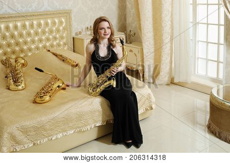 Pretty woman in black dress sits with sax on bed with wind instruments in baroque studio