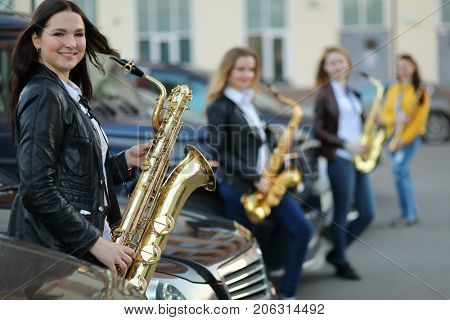 Four women play wind instruments outdoor near cars, focus on left woman