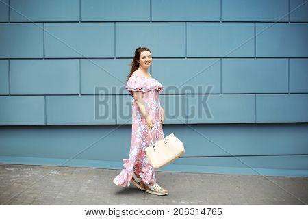 Beautiful overweight woman in pink ruffled dress walking on city street