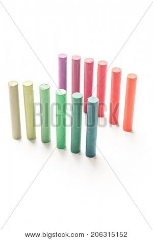 Bunch of standing colorful pastel chalks with color gradation, over white background