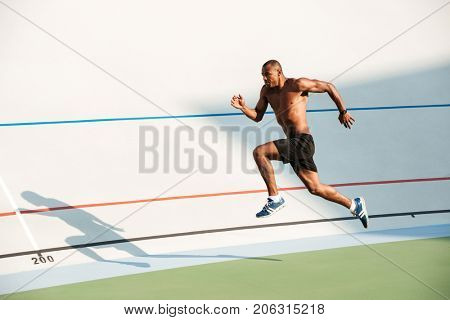 Full length portrait of a athletic half naked sportsman jumping on a track field outdoors