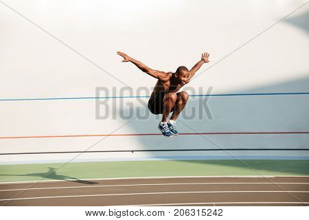Full length portrait of a half naked fit african sportsman doing a high jump at the track field outdoors