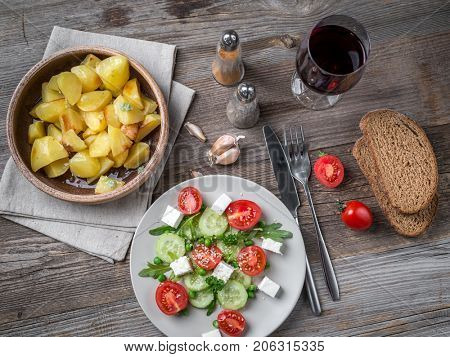 Served greek salad with feta cheese, glass of wine and baked potatoes in bowl, topview