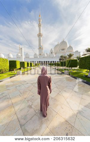 ABU DHABI, UAE - JAN 18, 2017: Woman and Sheikh Zayed Mosque is one of six largest mosques in world, mosque was officially opened in 2007