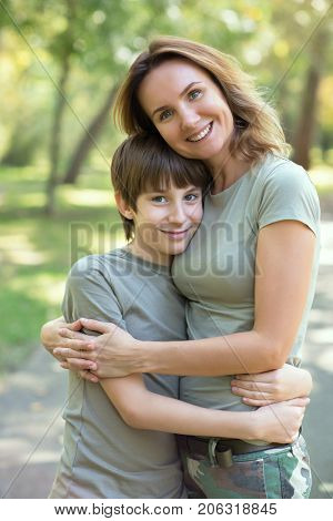 Happy mother and her 11 years old lovely son is embracing outdoor and looking at camera over autumn park background